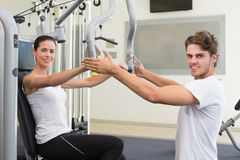 Fit brunette using weights machine for arms with trainer helping smiling at camera Stock Photos