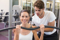 Fit brunette using weights machine for arms with trainer helping smiling at camera Royalty Free Stock Image