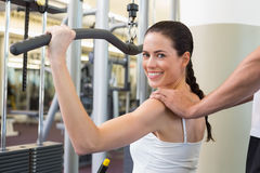 Fit brunette using weights machine for arms with trainer touching shoulders Royalty Free Stock Photos