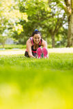 Fit brunette warming up on the grass Stock Photos