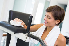 Fit brunette wiping down bench Royalty Free Stock Photo