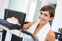 Fit brunette wiping down bench smiling at camera Royalty Free Stock Image