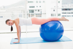 Fit brunette working out with exercise ball Stock Photos