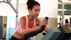 Fit brunette working out on the exercise bike Stock Photography