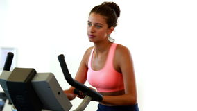 Fit brunette working out on the exercise bike Royalty Free Stock Photos