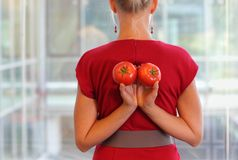 Fit business woman with tomatoes as a healhy snack - back view Stock Photo
