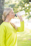 Fit calm blonde drinking from water bottle Royalty Free Stock Images