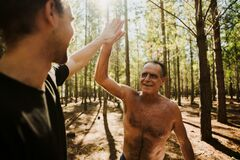 Fit caucasian elderly male high fiving his adult son after a tough run in the forest on fathers day