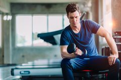 Fit caucasian handsome young man and big muscle in sportswear. Young man holding dumbbell stock photography