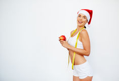 Fit for Christmas. Young woman with slim figure in Santa cap holding red apple and measuring tape Royalty Free Stock Photography