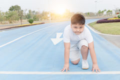 Fit and confident fat boy in starting position ready for running. Kid athlete about to start a sprint looking at camera with bright sunlight Stock Photography