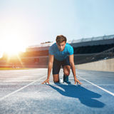 Fit and confident sprinter at starting blocks. Fit and confident man in starting position ready for running. Male athlete about to start a sprint looking at Stock Images
