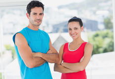 Fit couple with arms crossed in bright exercise room Royalty Free Stock Photo