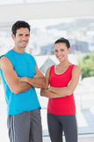 Fit couple with arms crossed in bright exercise room Stock Image