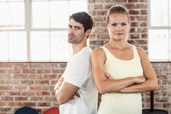 Fit couple with arms crossed in bright exercise room Stock Photo