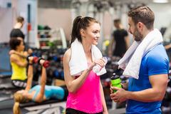 Fit couple chatting in weights room Stock Image