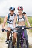 Fit couple cycling on mountain trail Stock Image
