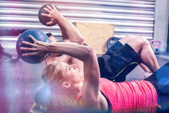 Fit couple doing abdominal ball exercise. At gym Royalty Free Stock Images