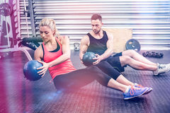 Fit couple doing abdominal ball exercise. At gym Stock Photos