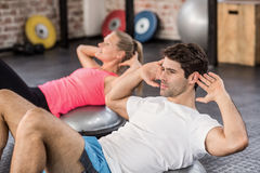 Fit couple doing abdominal crunches. In crossfit gym royalty free stock photo