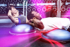 Fit couple doing bosu ball exercises Royalty Free Stock Image