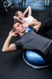 Fit couple doing sit ups on bosu ball Royalty Free Stock Images