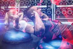 Fit couple doing sit ups on bosu ball. At gym Stock Photos