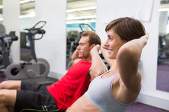 Fit couple doing sit ups on exercise ball Stock Photos