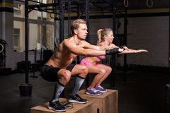 Fit couple doing squats on boxes in gym Royalty Free Stock Photo