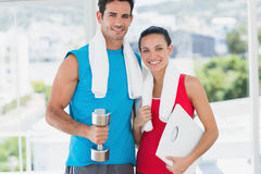 Fit couple with dumbbell and scale in bright exercise room Stock Photo