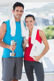Fit couple with dumbbell and scale in bright exercise room Stock Photos