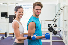 Fit couple exercising with blue dumbbells smiling at camera Royalty Free Stock Photography