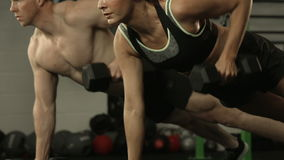 Fit couple exercising with dumbbells. In crossfit gym stock footage