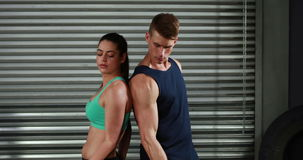Fit couple exercising with dumbbells. In garage stock video footage