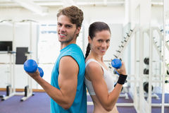 Fit couple exercising together with blue dumbbells Royalty Free Stock Photos