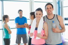 Fit couple with friends in background in exercise room Royalty Free Stock Photos