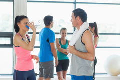 Fit couple with friends in background in exercise room Stock Photo