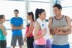 Fit couple with friends in background in exercise room Stock Images