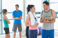 Fit couple with friends in background in exercise room Stock Photos