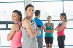 Fit couple with friends standing in background in exercise room Stock Images