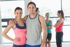Fit couple with friends standing in background in exercise room Stock Image
