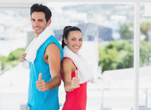 Fit couple gesturing thumbs up in bright exercise room Royalty Free Stock Image