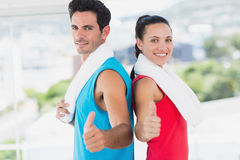 Fit couple gesturing thumbs up in bright exercise room Stock Image