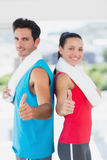 Fit couple gesturing thumbs up in bright exercise room Royalty Free Stock Photos