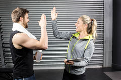 Fit couple high fiving in crossfit gym Stock Photos