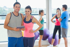Fit couple holding digital table with friends chatting in background Royalty Free Stock Photo