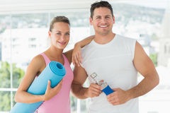 Fit couple holding water bottle and exercise mat in exercise room Royalty Free Stock Image