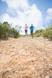 Fit couple jogging down mountain trail Royalty Free Stock Image