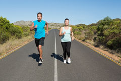 Fit couple jogging on the open road together Stock Images