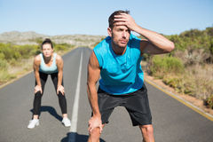 Fit couple jogging on the open road together Royalty Free Stock Photos